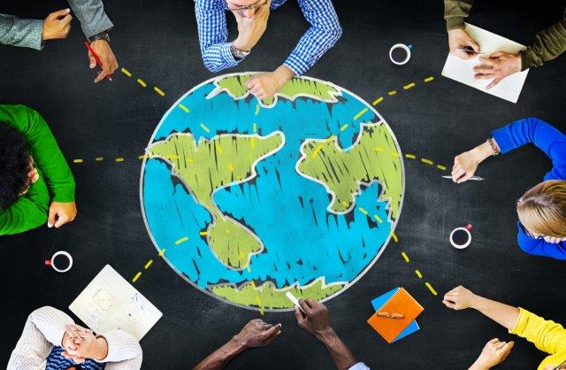 People sitting around chalk drawing of globe