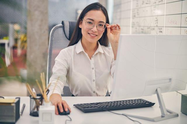 Smiling businesswoman in glasses sitting at desktop computer
