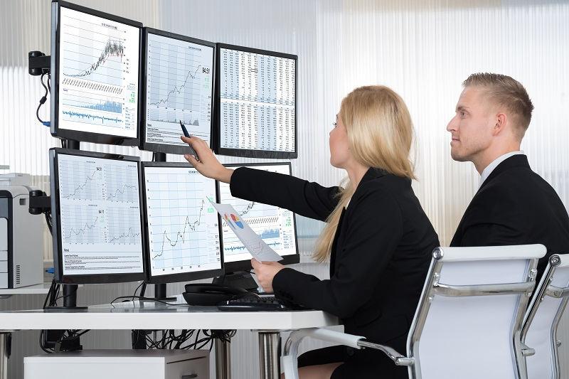 Why Should You Study Business Analytics? blog image - man and woman analyze business data on multiple screens